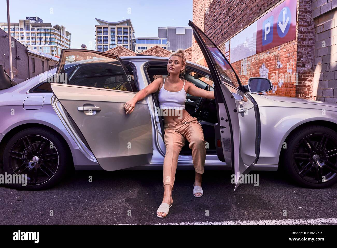 Australia, Adelaide, women fashion blogger and actress Sarah Jeavons posing in parked car - Stock Image