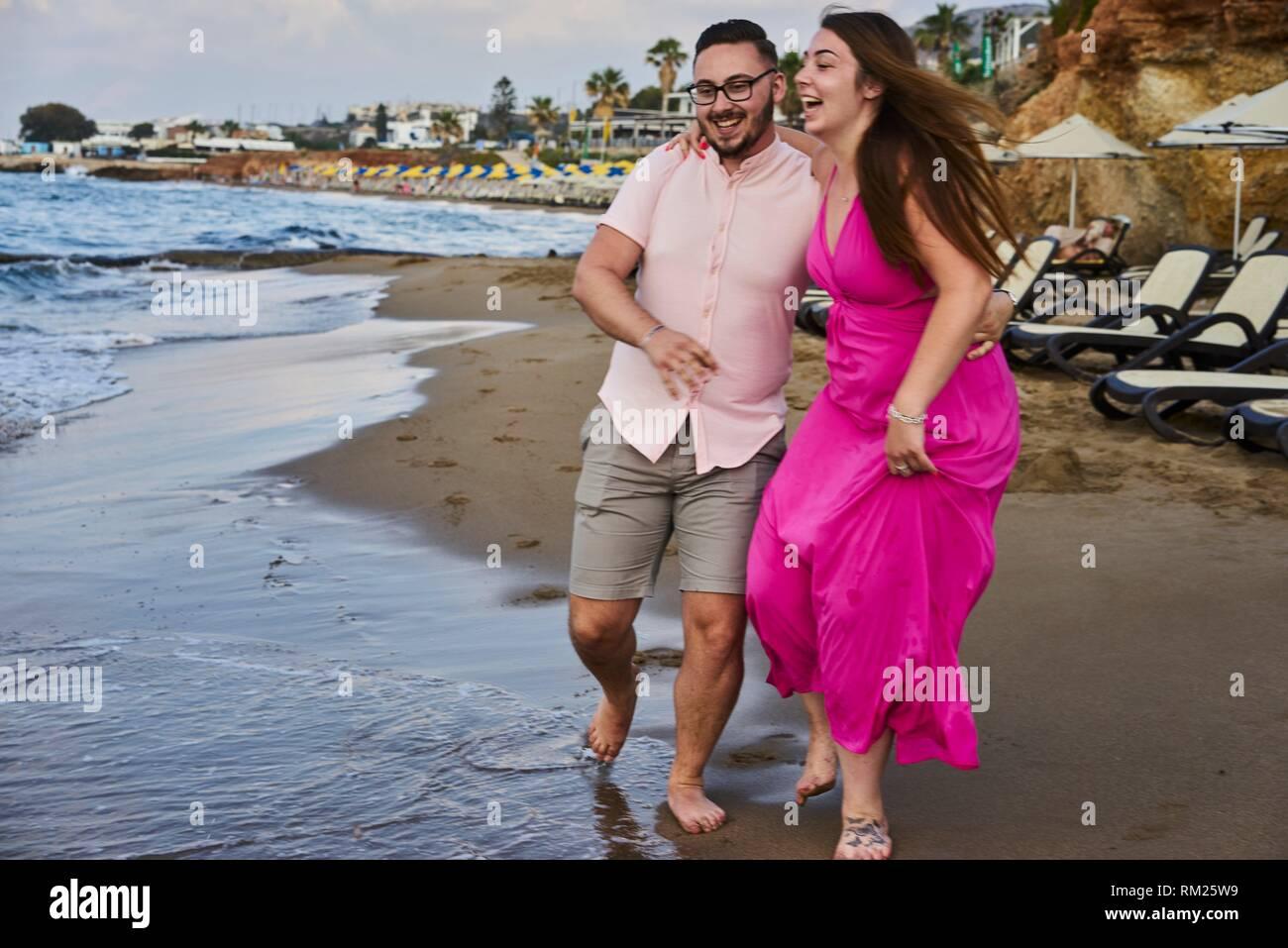 Chersonissos, Crete, Greece, couple running on beach, playful, teasing, joking, fun, holiday - Stock Image
