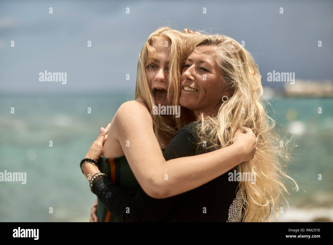 Mother (43 years) and teenage daughter (13 years) at seaside, bonding, embracing, screaming, motherhood, single parent. Danish ethnicity. - Stock Image