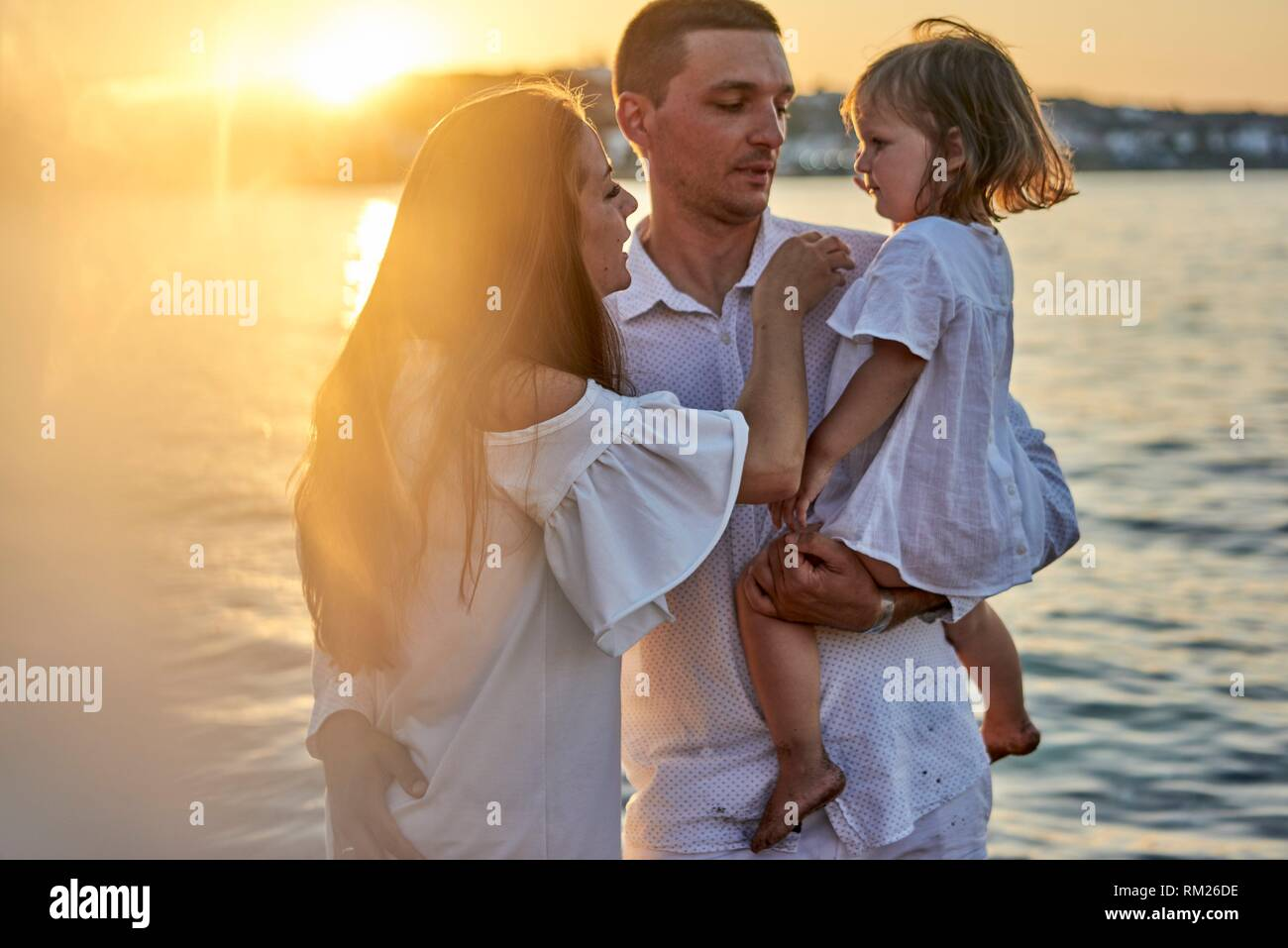 family, parenthood, sunset, candid, unposed, real people. In Chersonissos, Crete, Greece - Stock Image