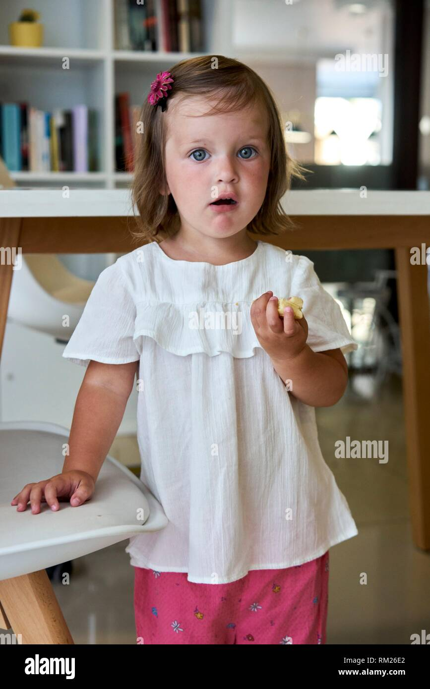 stunned child at home with food in hands - Stock Image