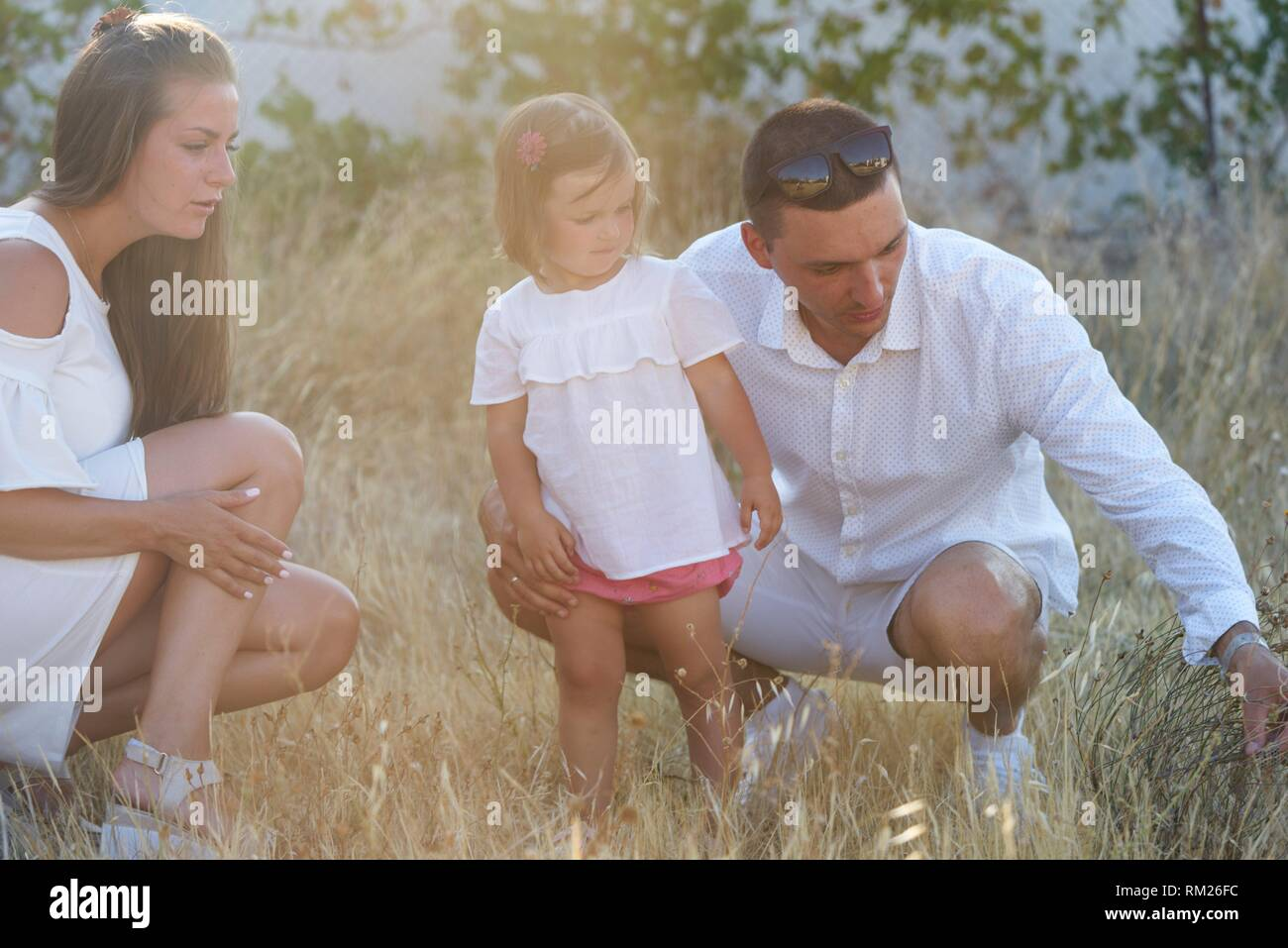 parents with toddler daughter exploring nature in garden - Stock Image