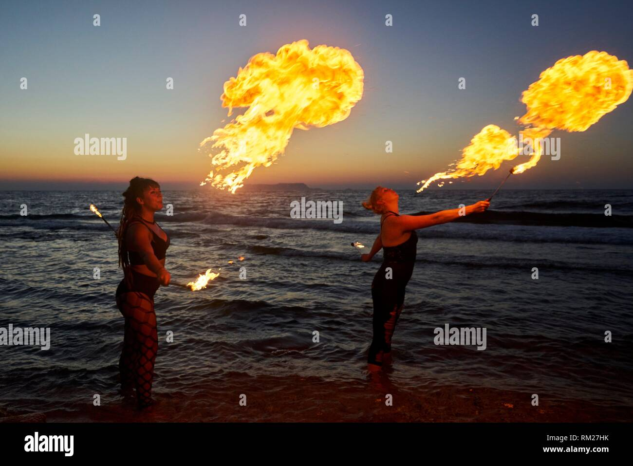 fire-breathing , beach, standing in sea water, in holiday destination Chersonissos, Crete, Greece. - Stock Image