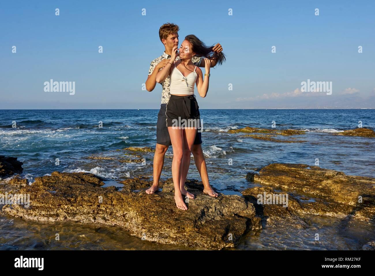 Couple standing on rocks, seaside, holiday, love, lovers. Chersonissos, Crete, Greece. - Stock Image