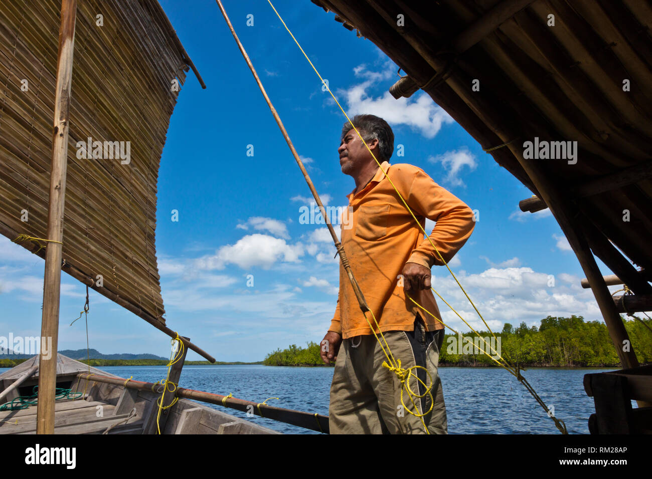 A MOKEN MAN sails his traditional boat to KHO RA ISLAND in the Andaman Sea - THAILAND - Stock Image