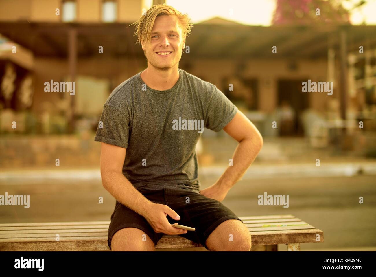 Man with smartphone sitting on bench at street, Stalida, Crete, Greece. Stock Photo