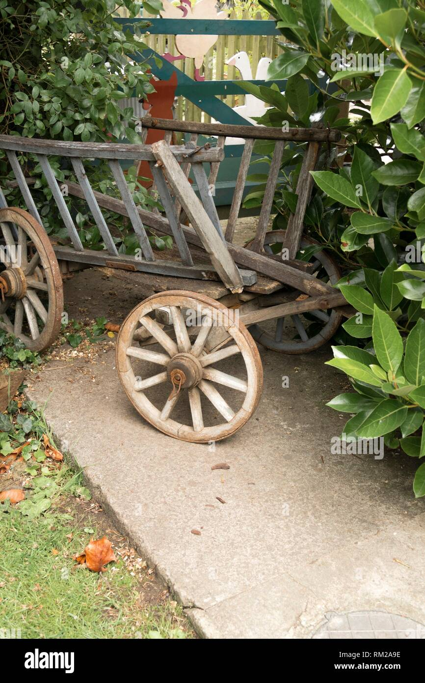 Old fashioned, weathered ´haywain´ child´s pull-along garden toy parked in the shrubbery by a garden gate in Frampton on Severn, the Cotswolds, - Stock Image