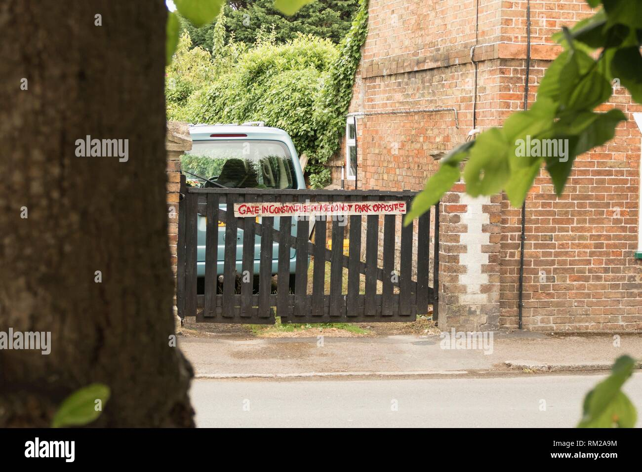 ´Please do not park opposite´, hand written sign in red paint attached to a gate in Frampton on Severn, the Cotswolds, England. - Stock Image