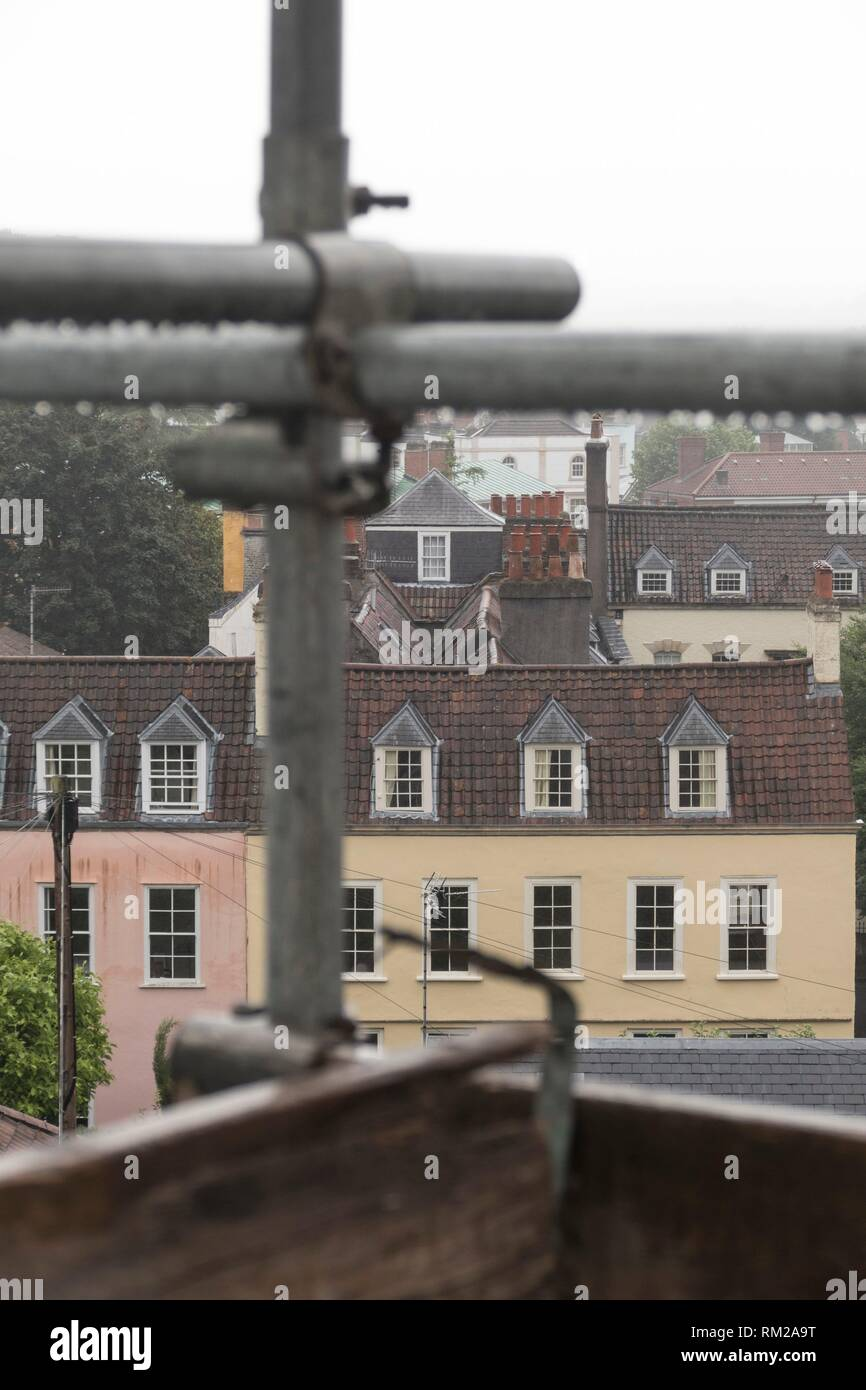 Metal scaffolding poles after the rain, looking out over the historic rooftops and chimneys of Hotwells, Bristol, England. - Stock Image