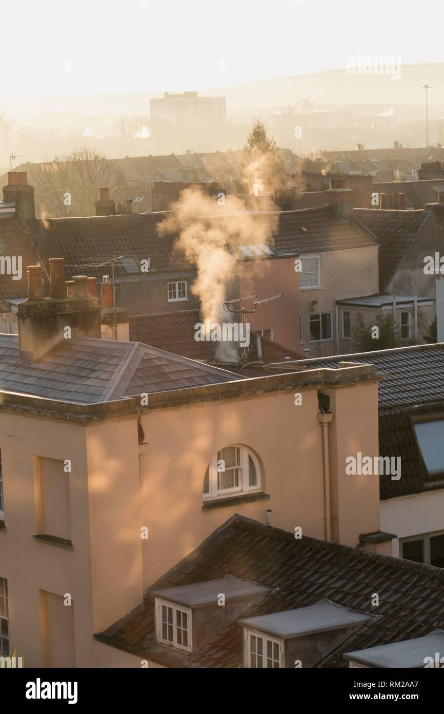 Dappled sunlight and plumes of white smoke curling upwards on a frosty day from the historic rooftops of Hotwells, Bristol, England. - Stock Image