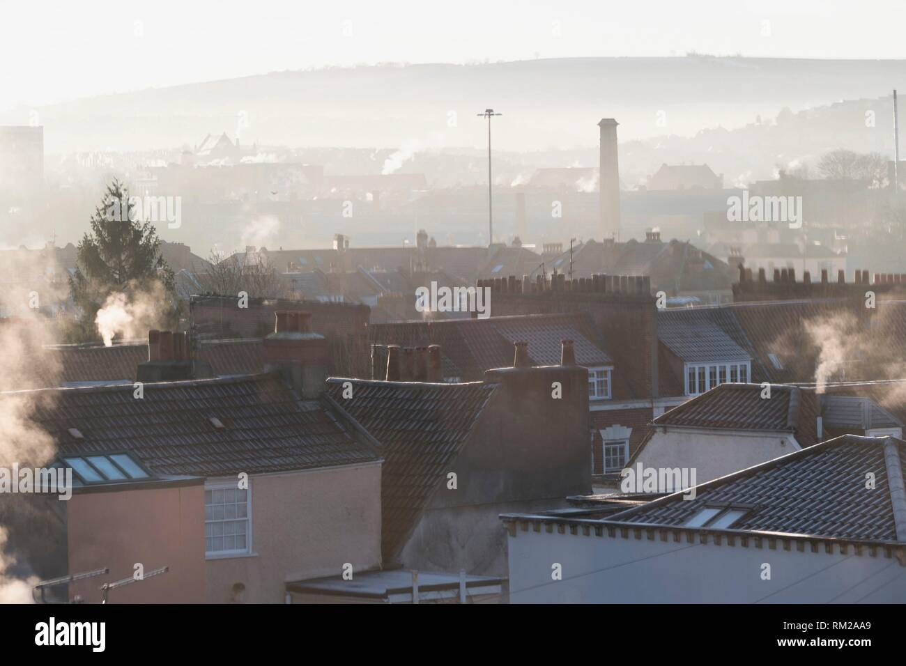 Frosty rooftops, smoking chimneys and muted tones as the sun rises over the harbour in Hotwells, Bristol, England. - Stock Image