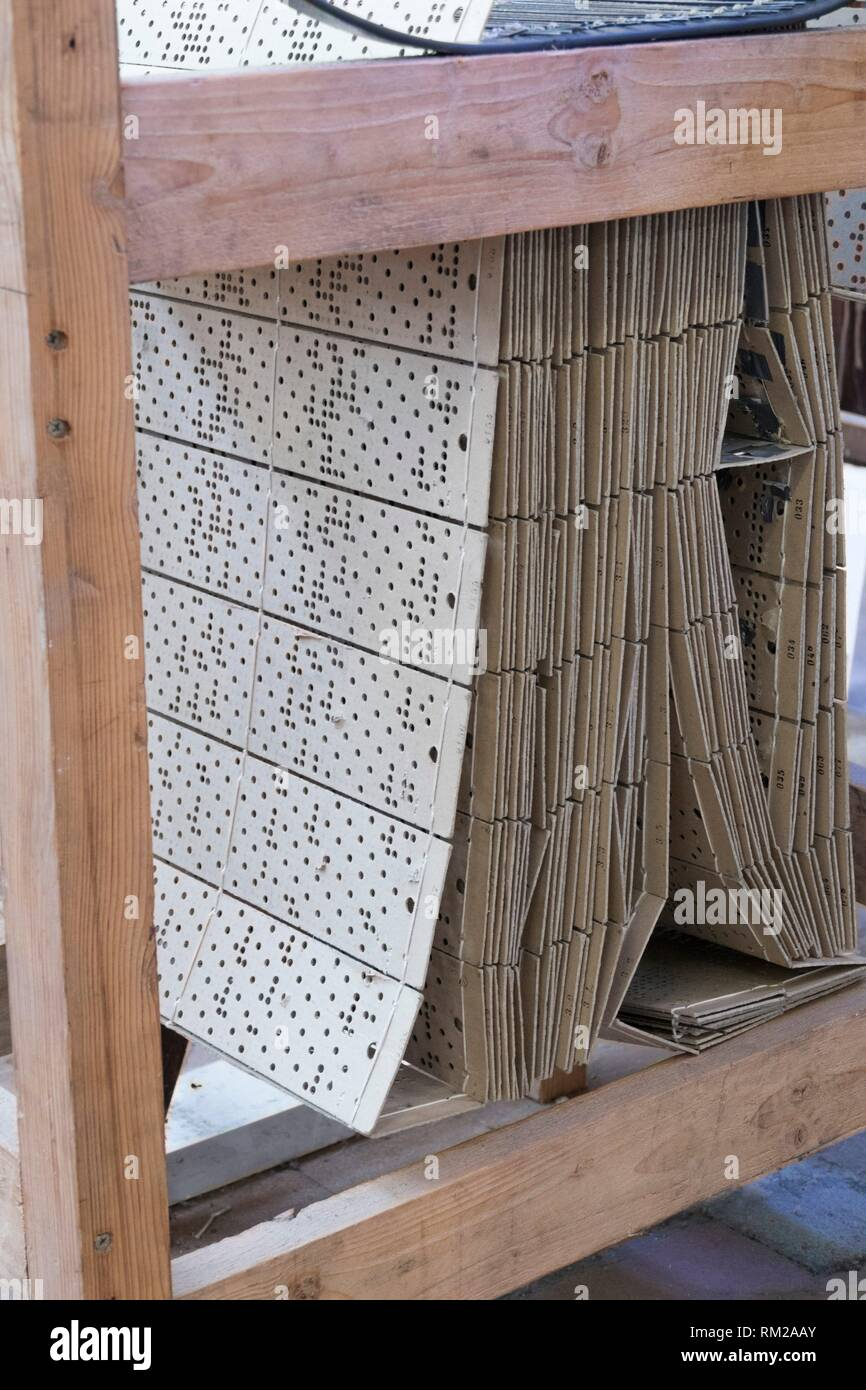 Neutral buff coloured perforated pattern punch cards laced together for traditional jacquard weaving, La Manufacture de Roubaix, France. - Stock Image