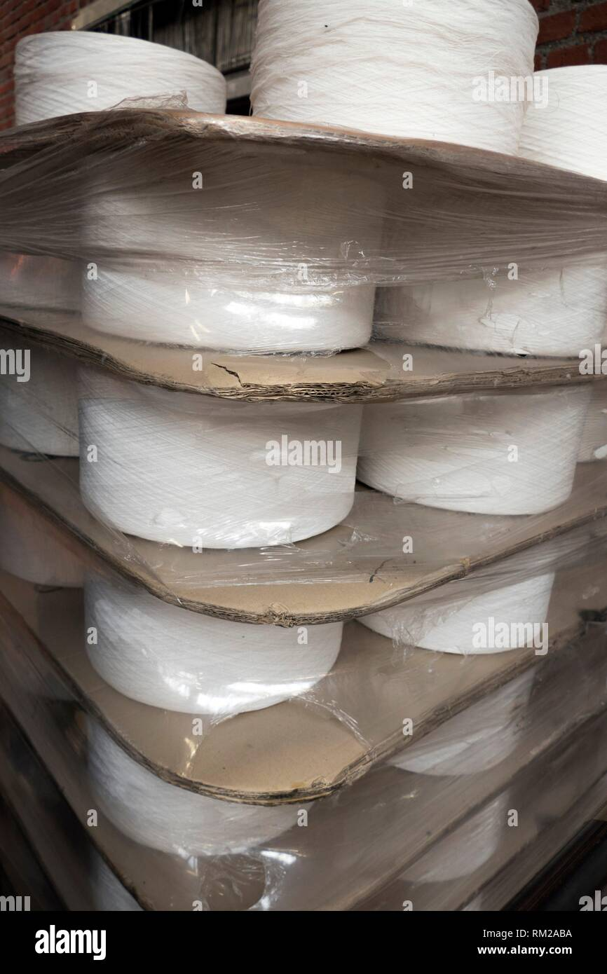 Confrontational flat industrial spools of white thread packaged with layers of thick corrugated card dividers and shrink wrapped in reflective - Stock Image