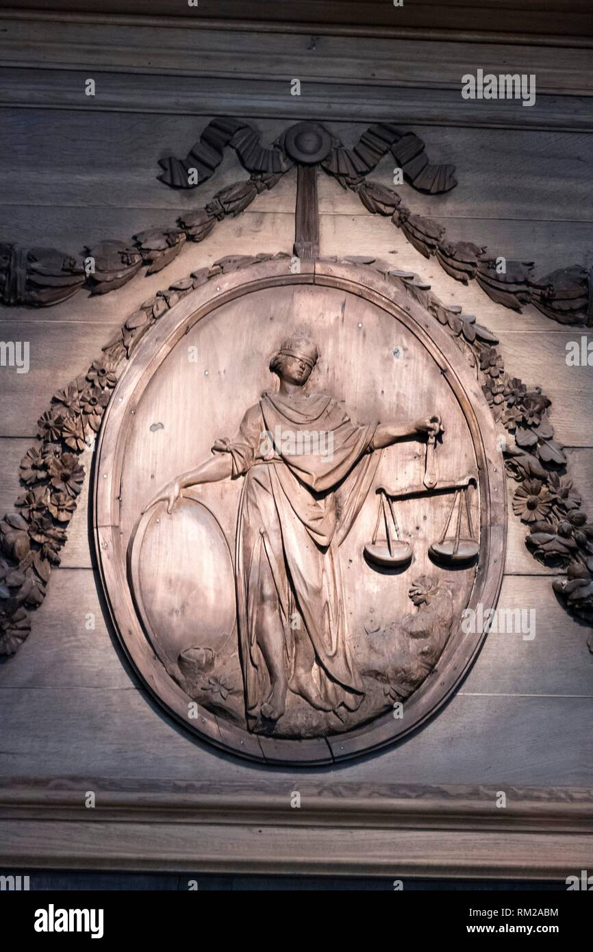 Classical oval wooden panel engraving showing Justice with blindfold and scales, surrounded by decorative foliage swags, Museum of Flanders, Cassel, - Stock Image