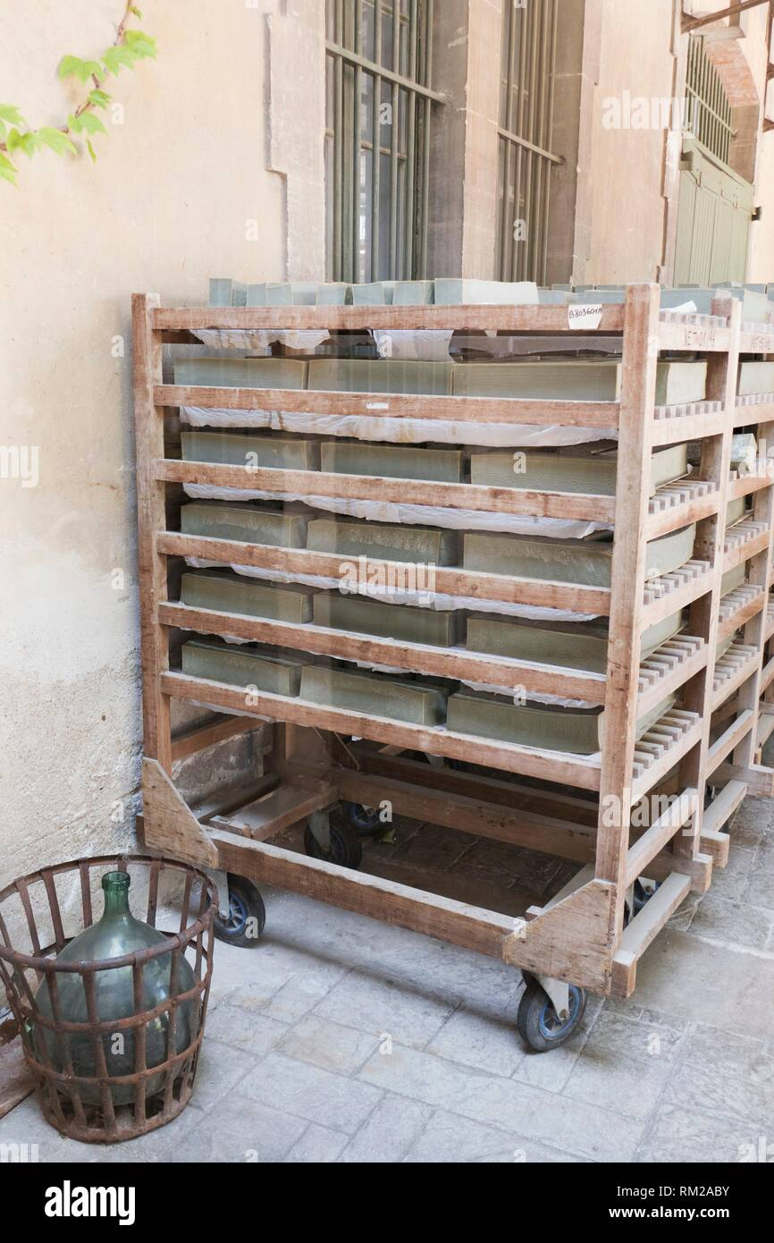 Mellow green blocks of olive Marseille soap on traditional wooden racks drying in the sun outside the Marius Fabre soap factory, Salon, Provence, Stock Photo