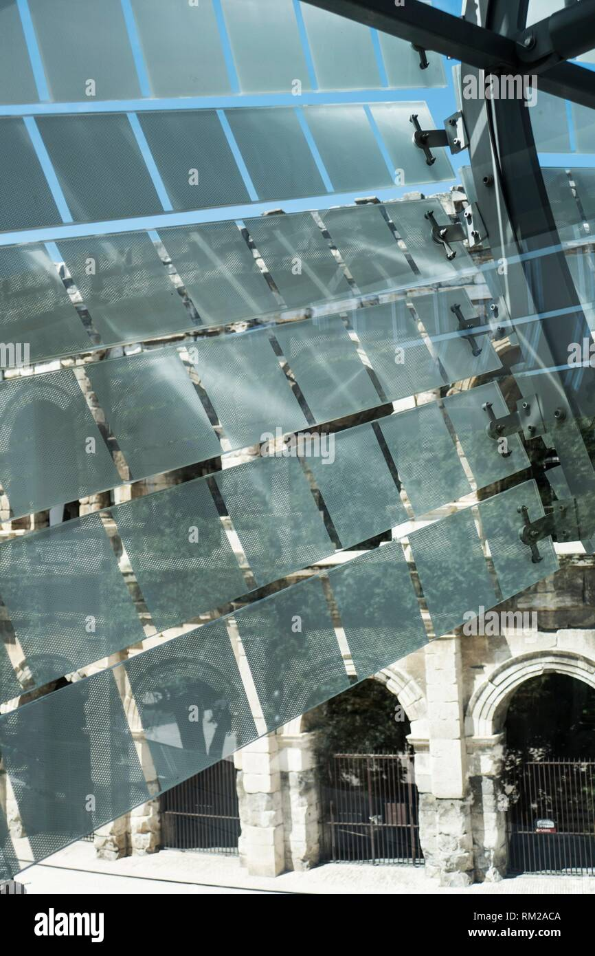 Glass and stainless steel light deflectors flutter like bunting on the facade of the Roman Museum at Nimes to reveal the massive stone arches of the - Stock Image