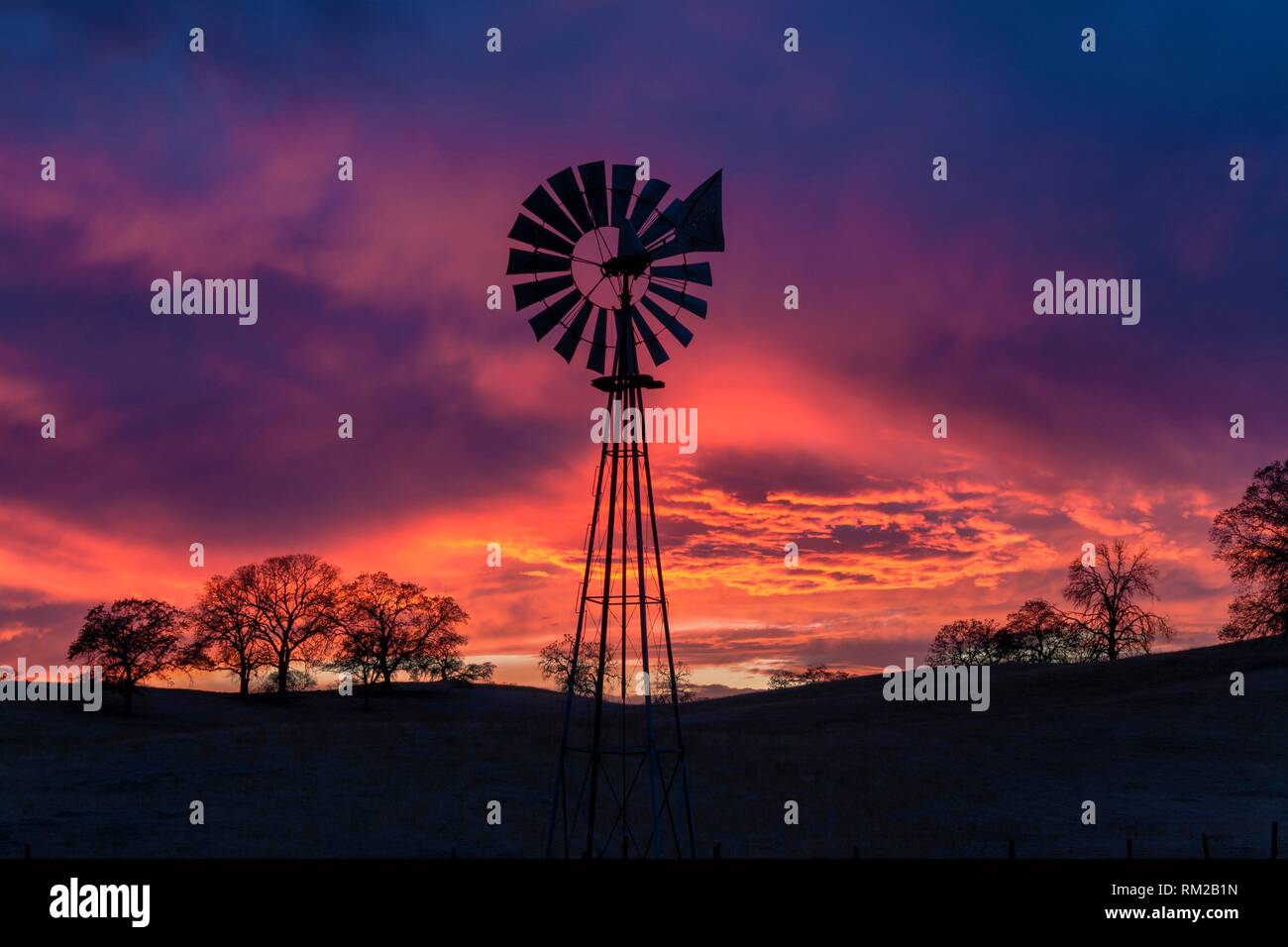 Sunset storm clouds and colors form a backdrop for a foothill farm´s windmill. Sierra Nevada Foothills, California, USA - Stock Image