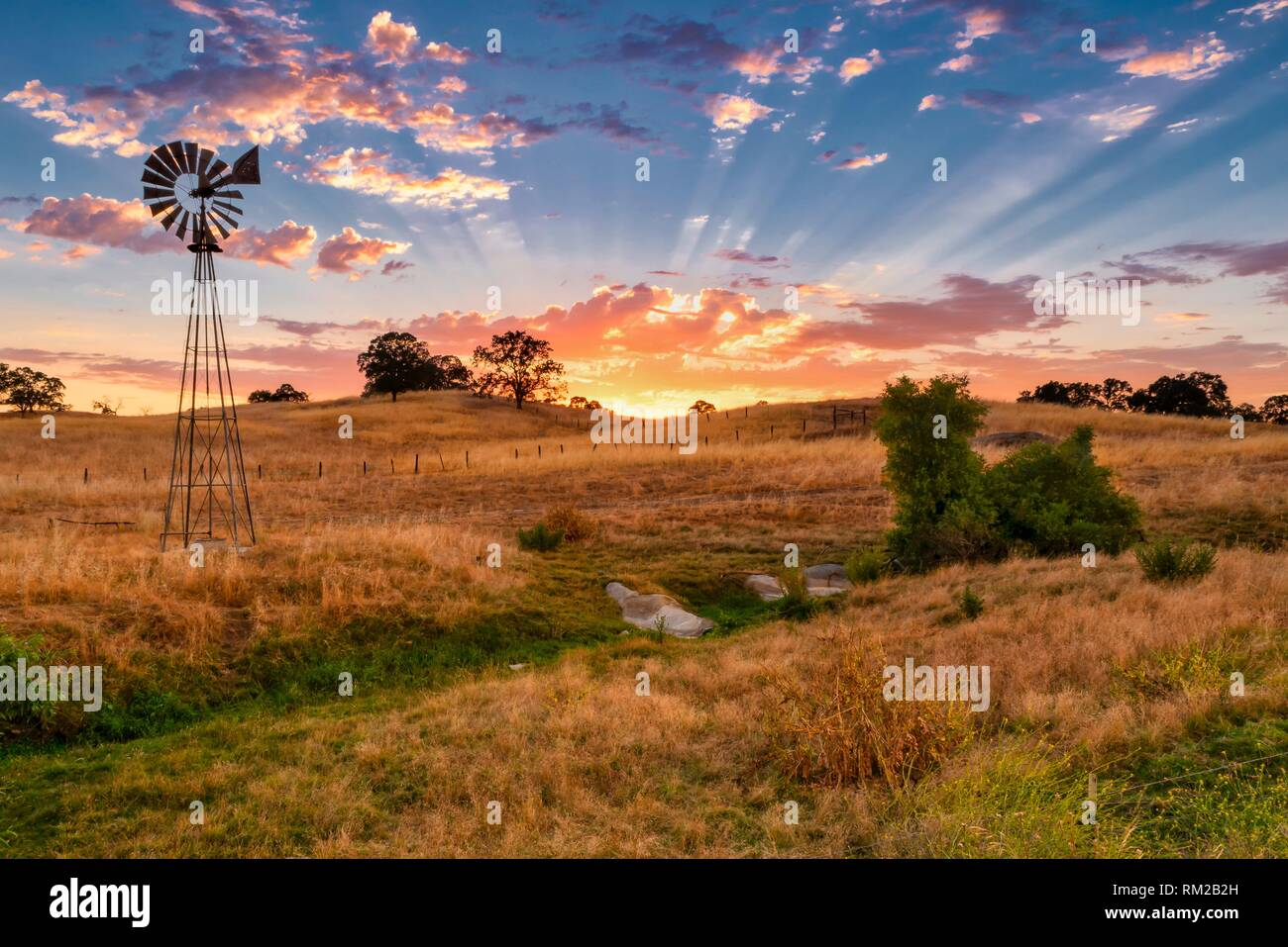 Windmill at Sunset in foothills of Central California. - Stock Image