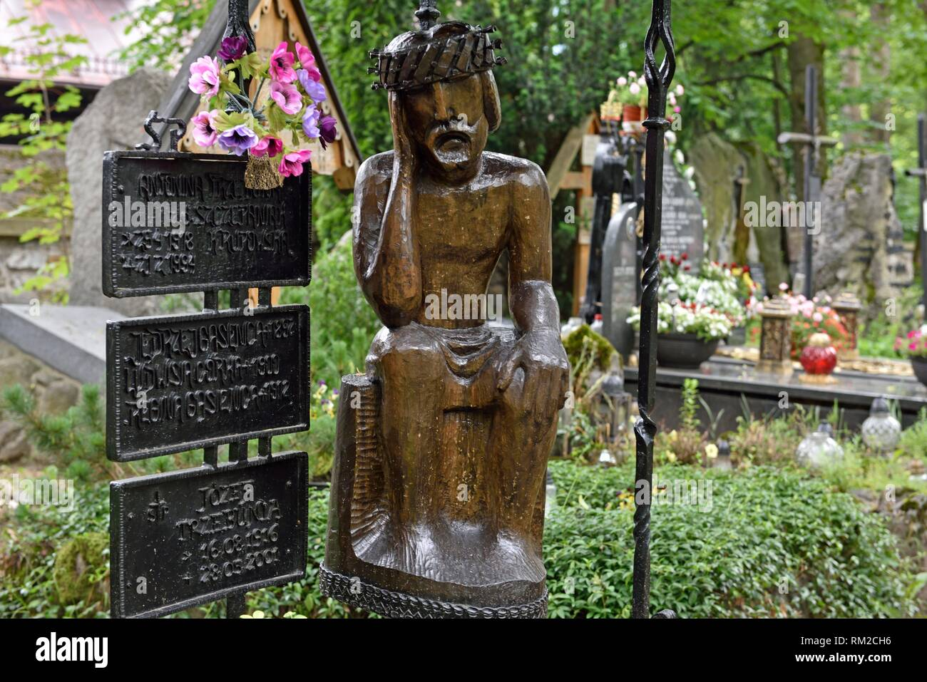 representation of ´´Worried´´ or ´´Distressed´´ Christ, related to the Polish folk culture, on wooden funerary stela in the old cemetery of Zakopane, - Stock Image