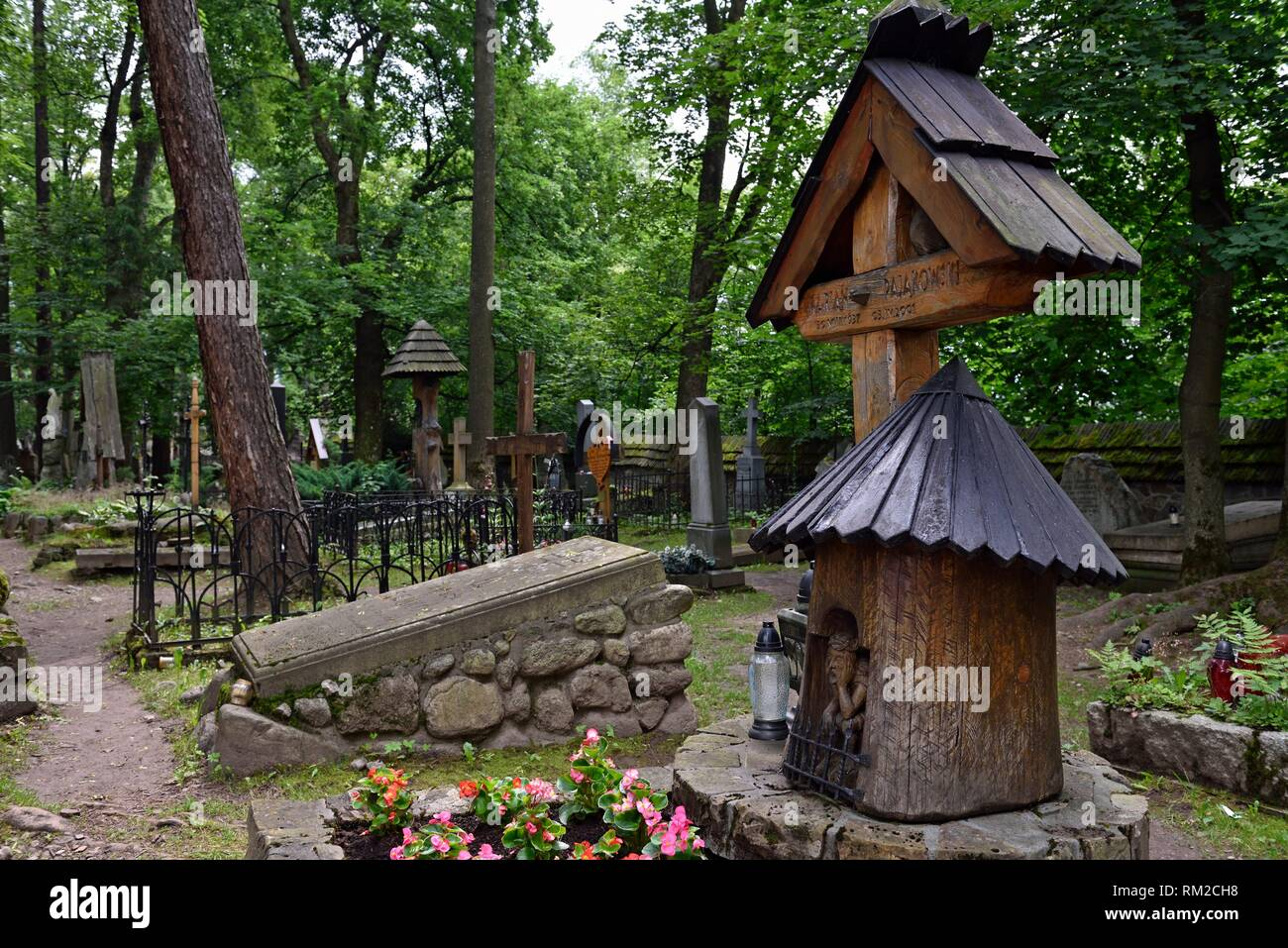 representation of ´´Worried´´ or ´´Distressed´´ Christ, related to the Polish folk culture, on wooden funerary stela in the old cemetery of Zakopane, Stock Photo