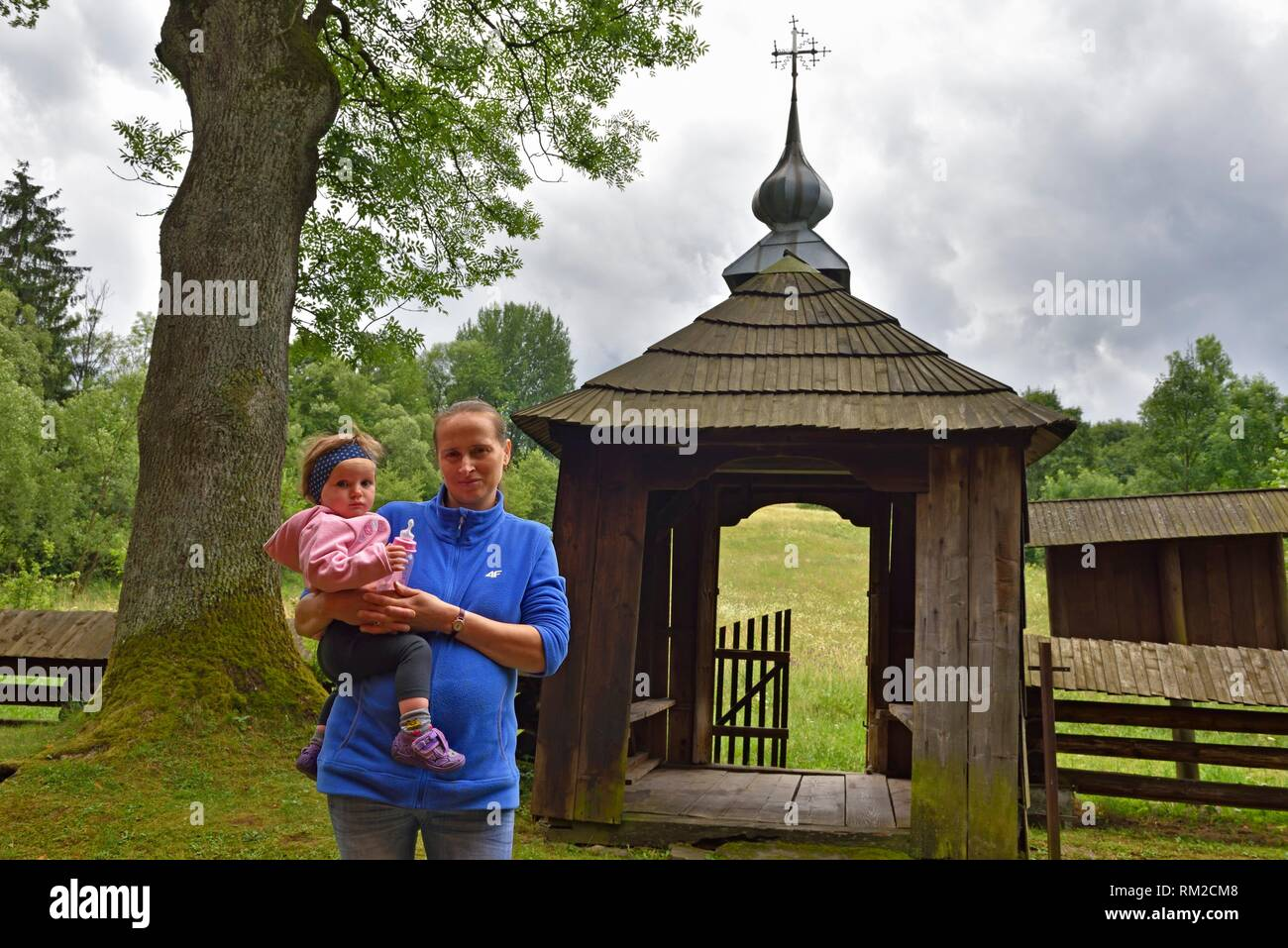 woman holding her child at the entrance of the Greek Catholic church of St. Paraskevia in the village of Nowica, commune of Uscie Gorlickie, Gorlice Stock Photo