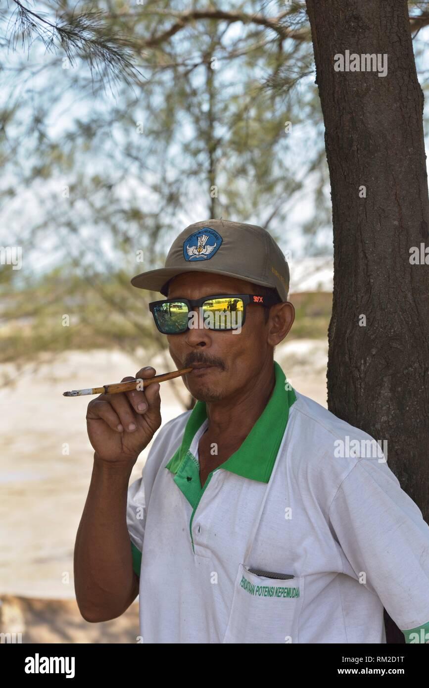 man using a cigarette holder to smoke a kretek, Punjulharjo Village near Lasem, Java island, Indonesia, Southeast Asia. - Stock Image