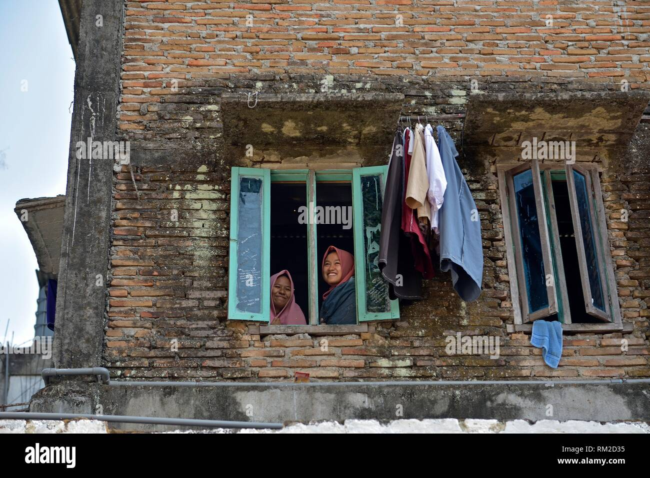 school girls at the window of a high school dormitory, Lasem, Java island, Indonesia, Southeast Asia. - Stock Image