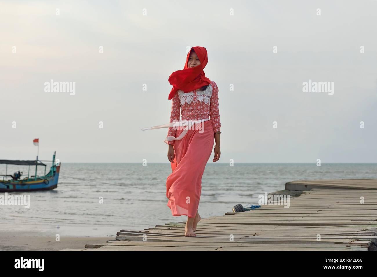 young woman walking on a pontoon at Karangjahe Beach near Lasem, Java island, Indonesia, Southeast Asia. - Stock Image