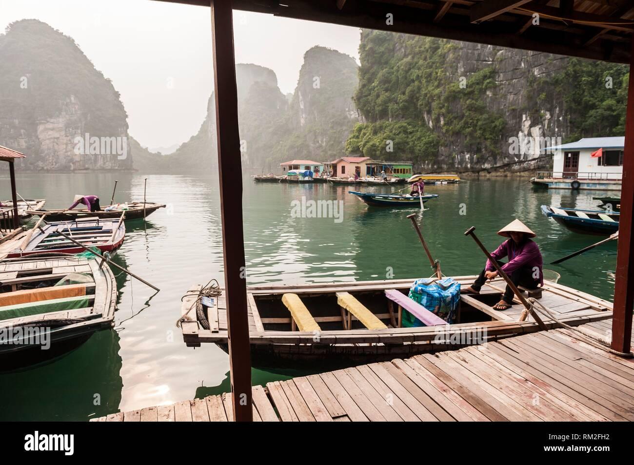 Vietnamese boatman in the karst landscape of Ha Long Bay, Quang Ninh Province, Vietnam. Ha Long Bay is a UNESCO World Heritage Site. Stock Photo