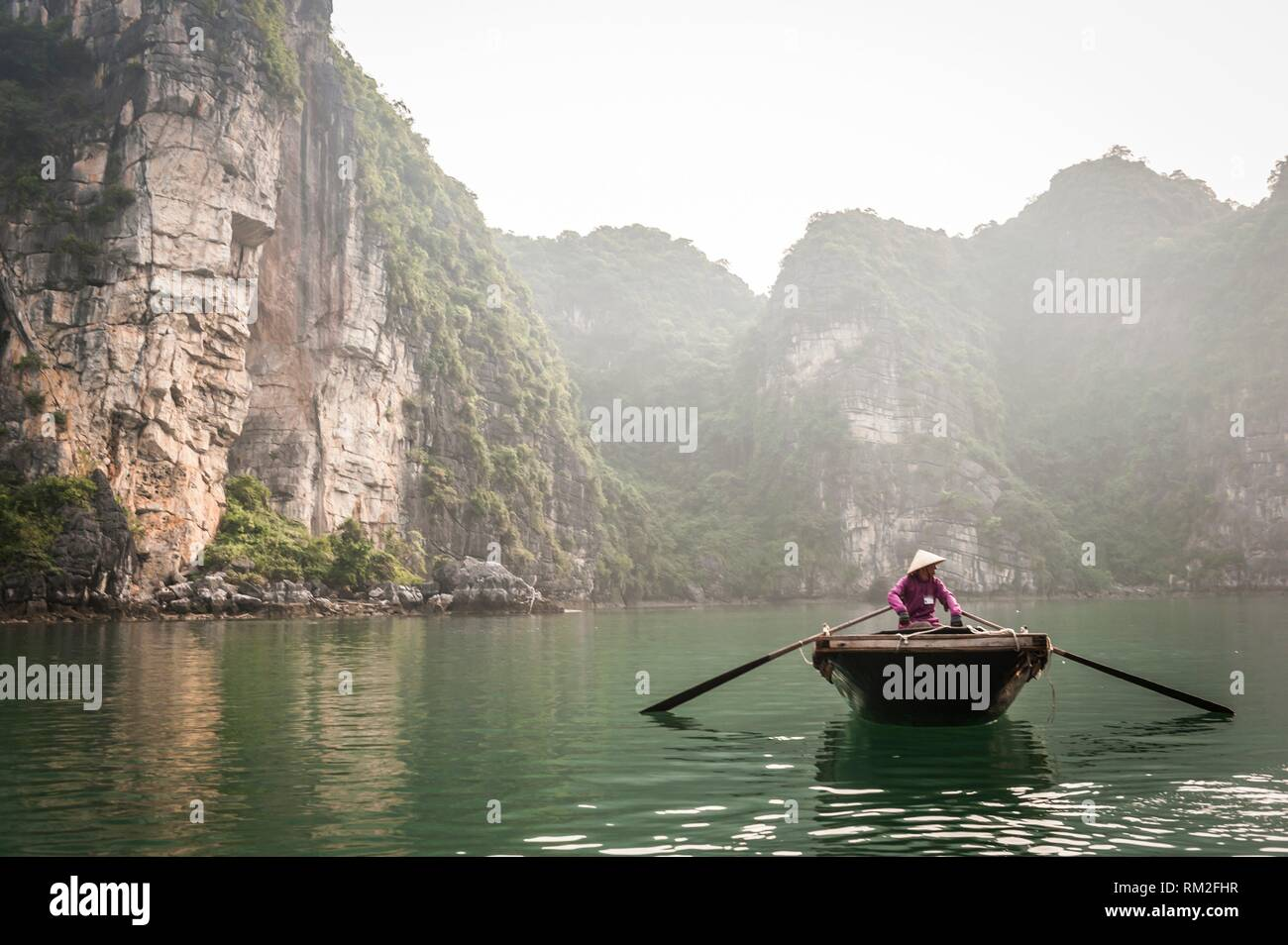 Vietnamese boatman in the karst landscape of Ha Long Bay, Quang Ninh Province, Vietnam. Ha Long Bay is a UNESCO World Heritage Site. Stock Photo