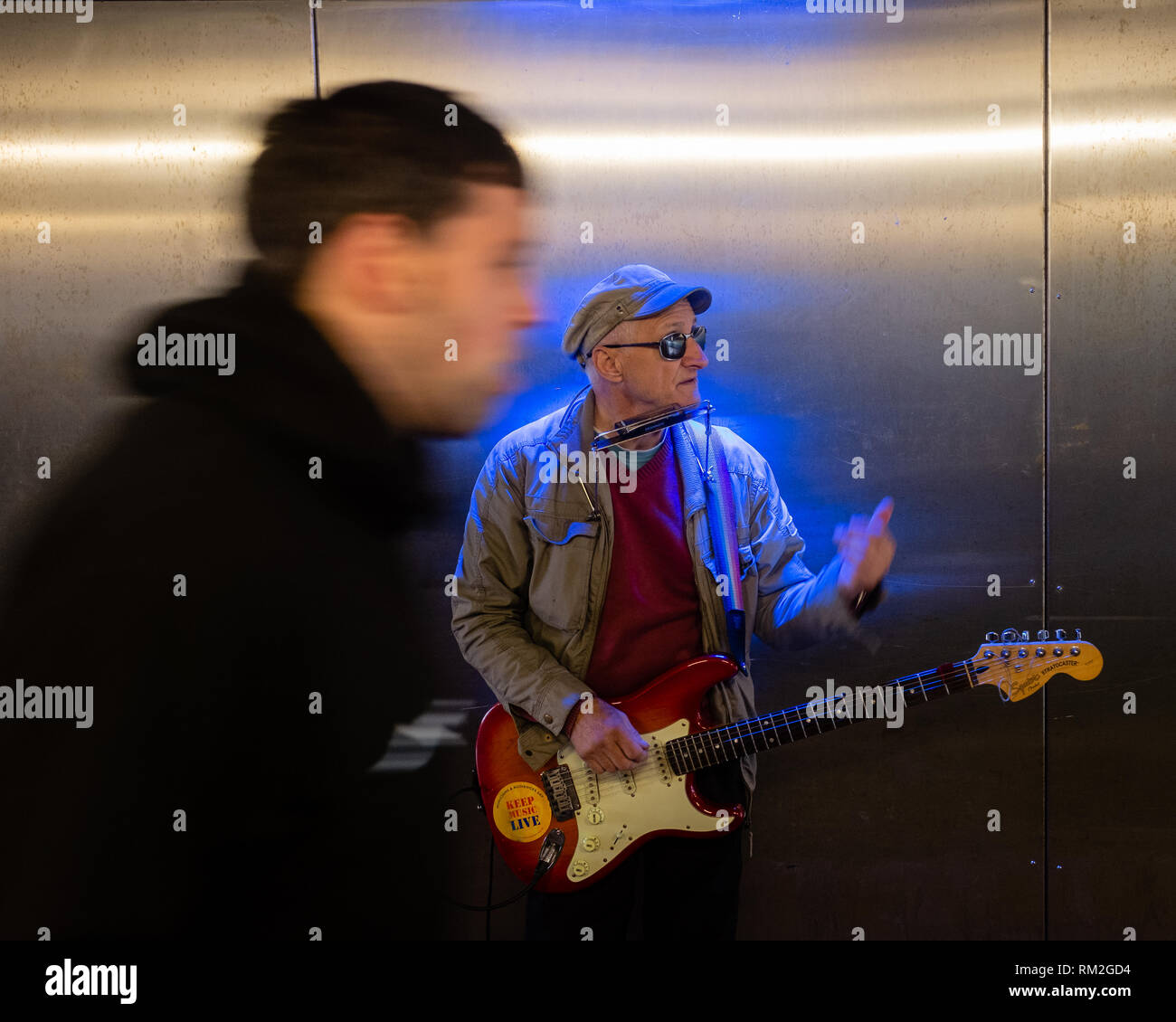 Male busker fort william underpass entertains as strangers pass by - Stock Image