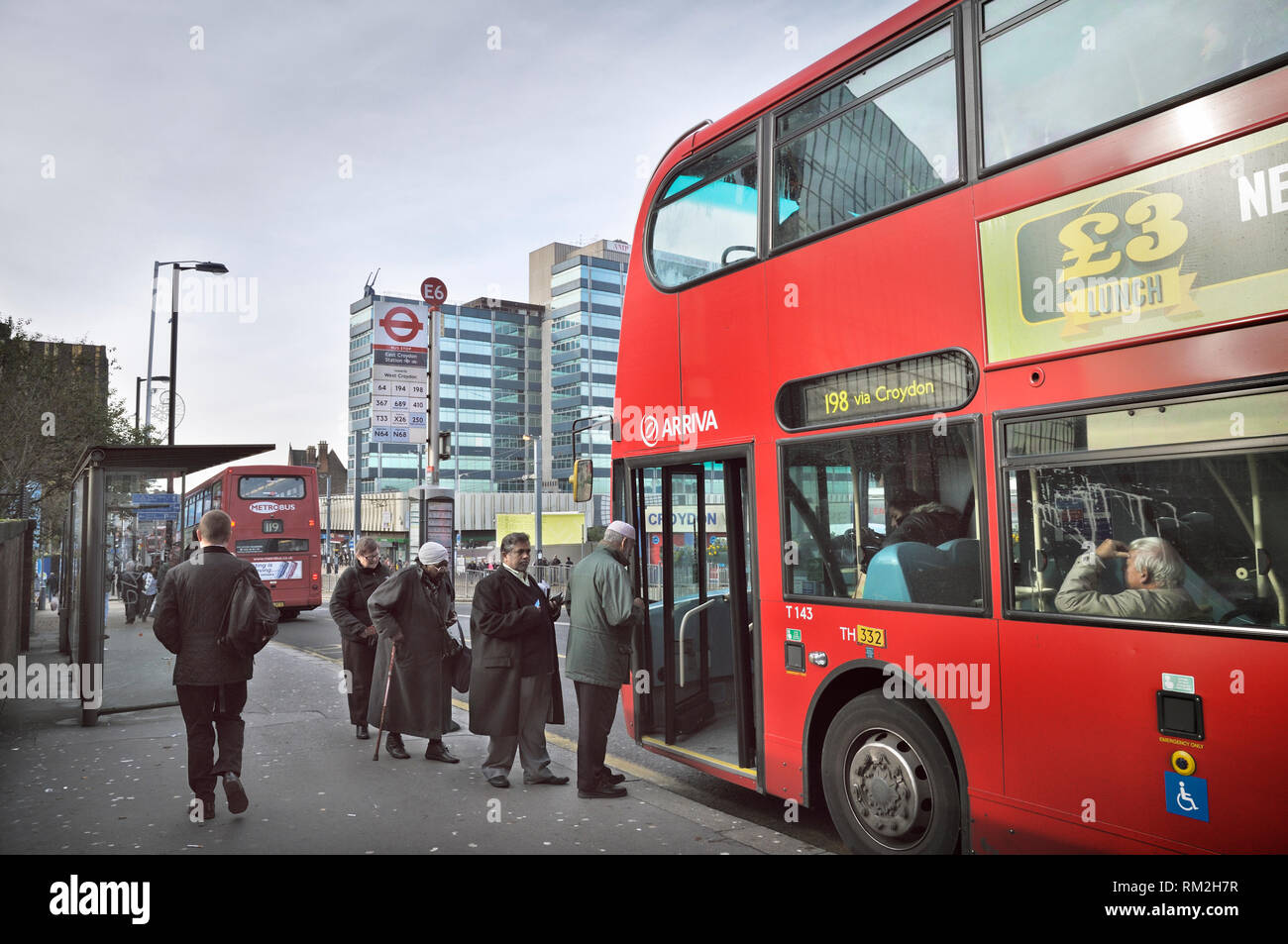 Senior people waiting to board a bus in Croydon, South London, England, UK - Stock Image
