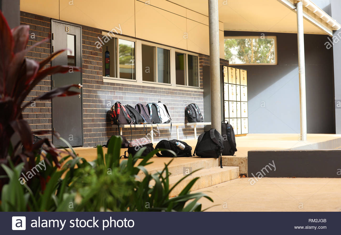 modern high school classroom in an educational facility. Student school bags scattered around with lockers in the background. School yard - Stock Image