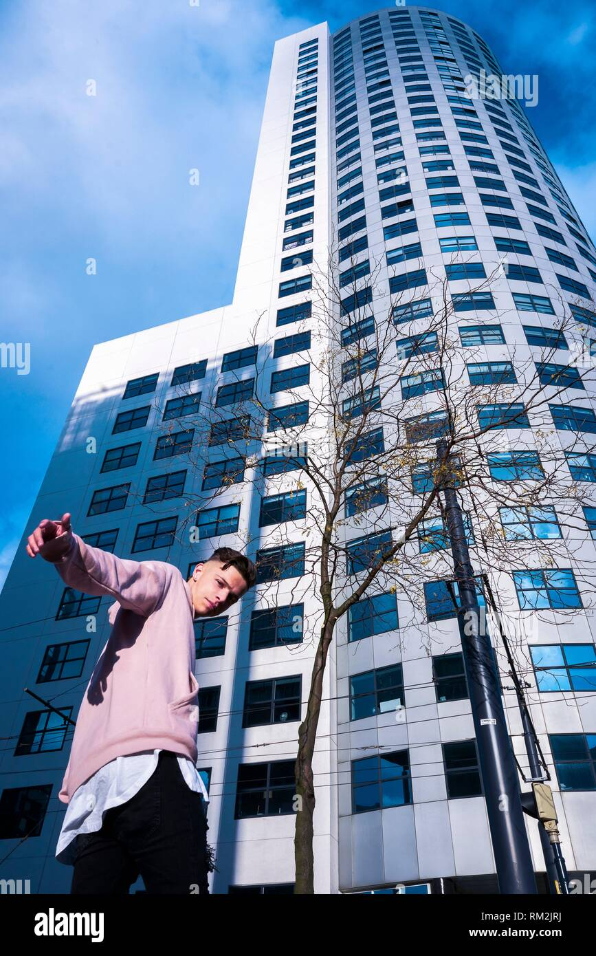 teenager in modern casual clothes going to high business tower, with inviting gesture. Dutch ethnicity. In Rotterdam, Netherlands - Stock Image