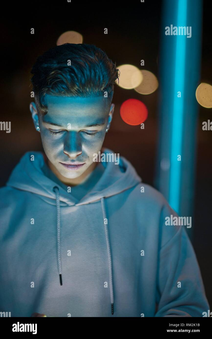 teenager with closed eyes in colourful city lights. Dutch ethnicity. 18 years old. - Stock Image