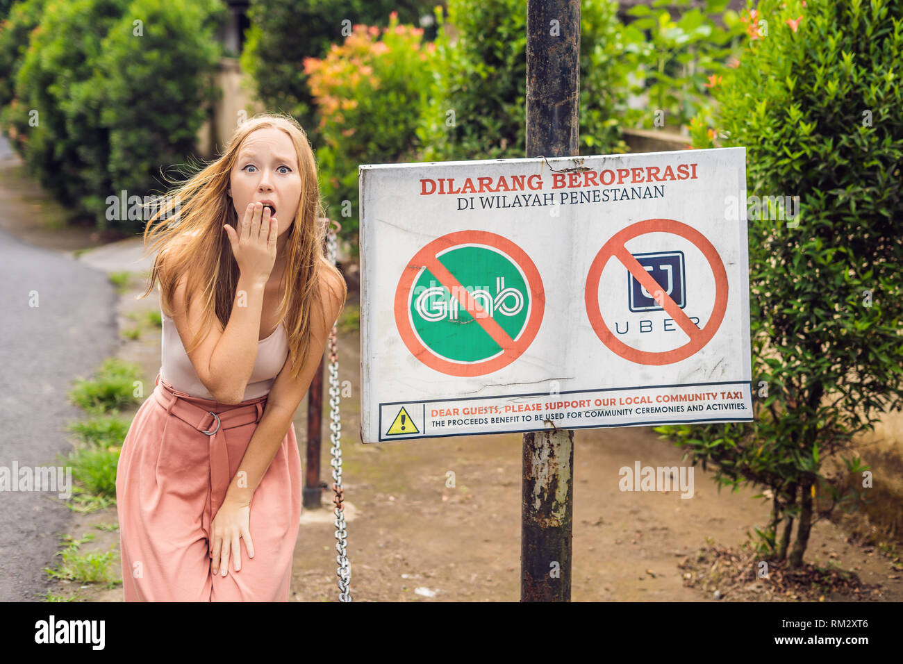 BALI, INDONESIA - 21 May, 2018: Young woman looks at protest sign on a wall in Indonesian objecting to Uber and Grab taxi drivers reads 'Uber and Grab - Stock Image