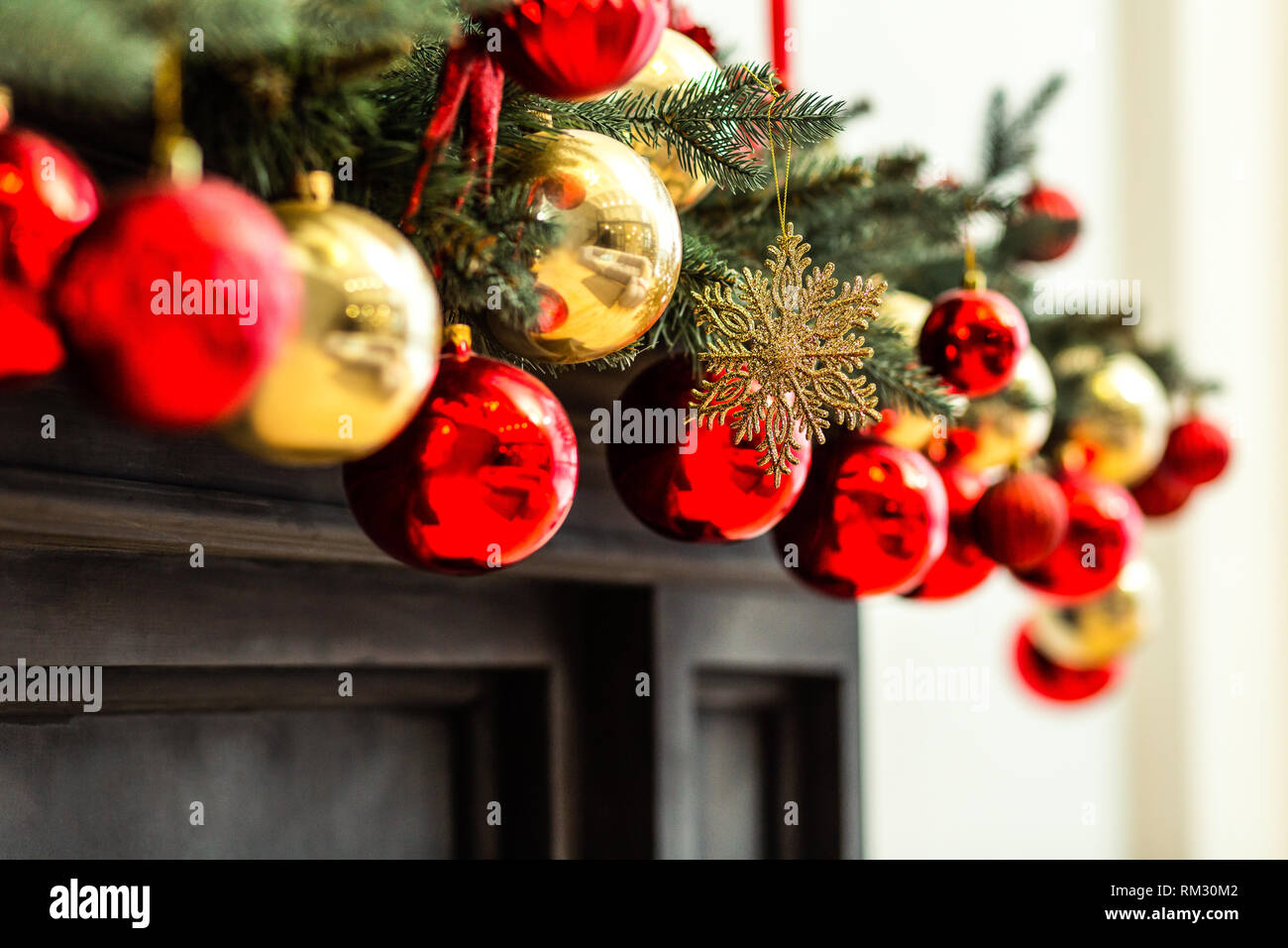 Red and golden christmas ornaments hanging from the christmas tree - Stock Image