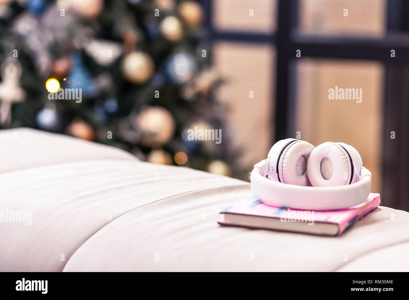 Pink earphones and a sketch-book laying on the pinky sofa in the room - Stock Image