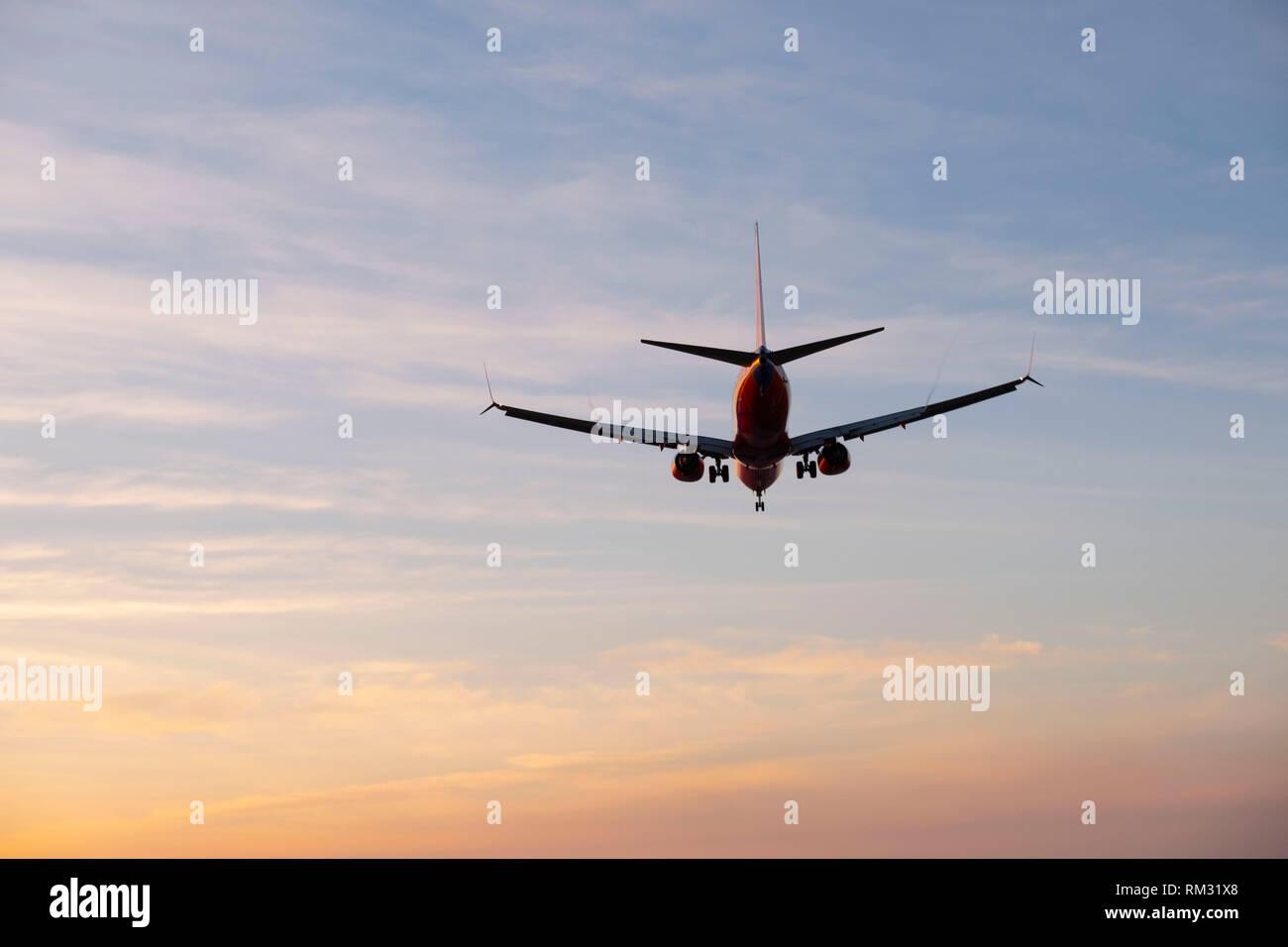 Passenger Jet flying at sunset - Stock Image