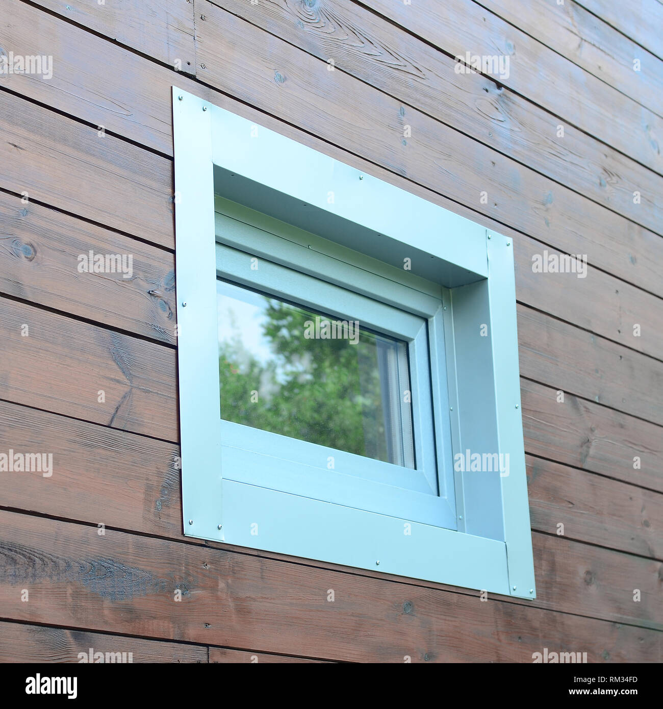 Plastic PVC window in modern passive wooden house facade wall. PVC windows are the number one in house energy efficiency - Stock Image
