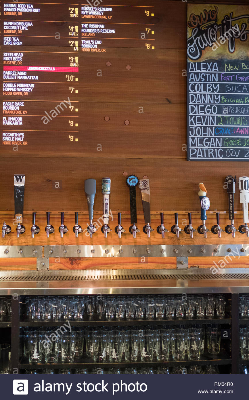 Projected drink menu on wall above many beer taps in the Tap and Growler, Eugene, Lane County, Oregon, USA - Stock Image