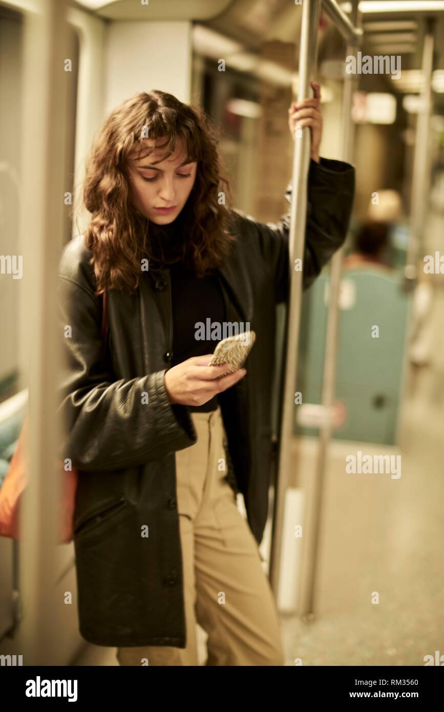 Woman in public transport, using smartphone, Berlin, Germany. Stock Photo