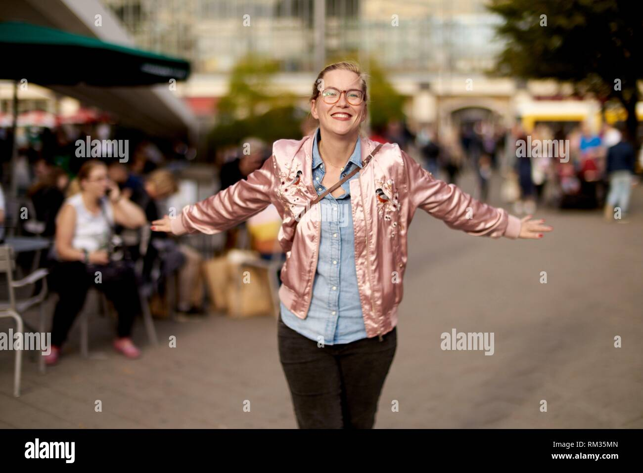Lively woman with open arms dancing at Alexanderplatz, Berlin, Germany Stock Photo