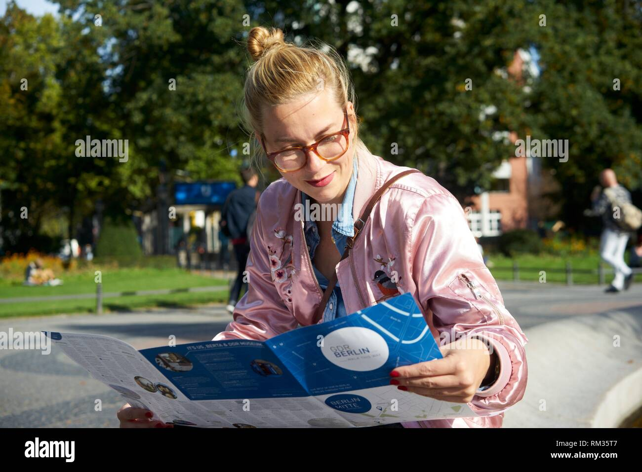 Woman reading city guide map, in berlin, germany stock photo.