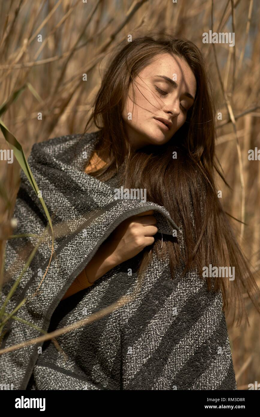 Young woman in undergrowth, wrapped in towel. Crete, Greece. Stock Photo