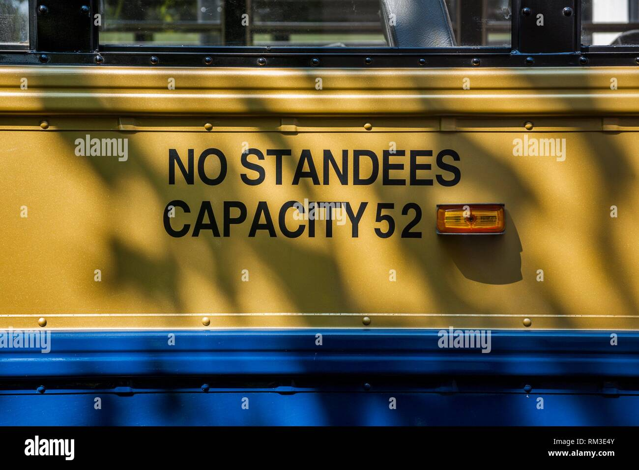 '''''No Standees-Capacity 52'' sign written on side of a yellow school bus. - Stock Image