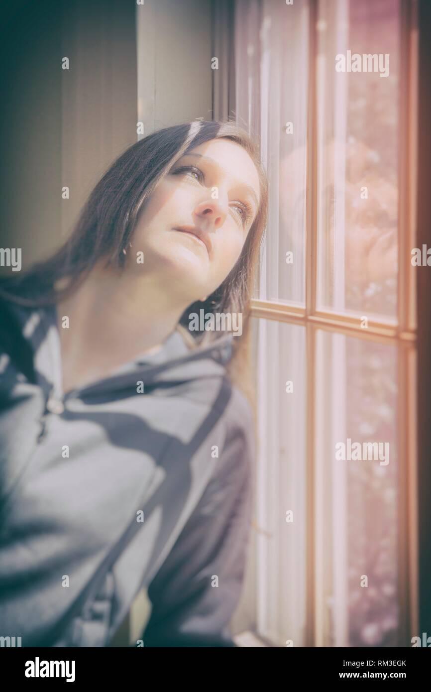 Young woman leaning against a window. - Stock Image