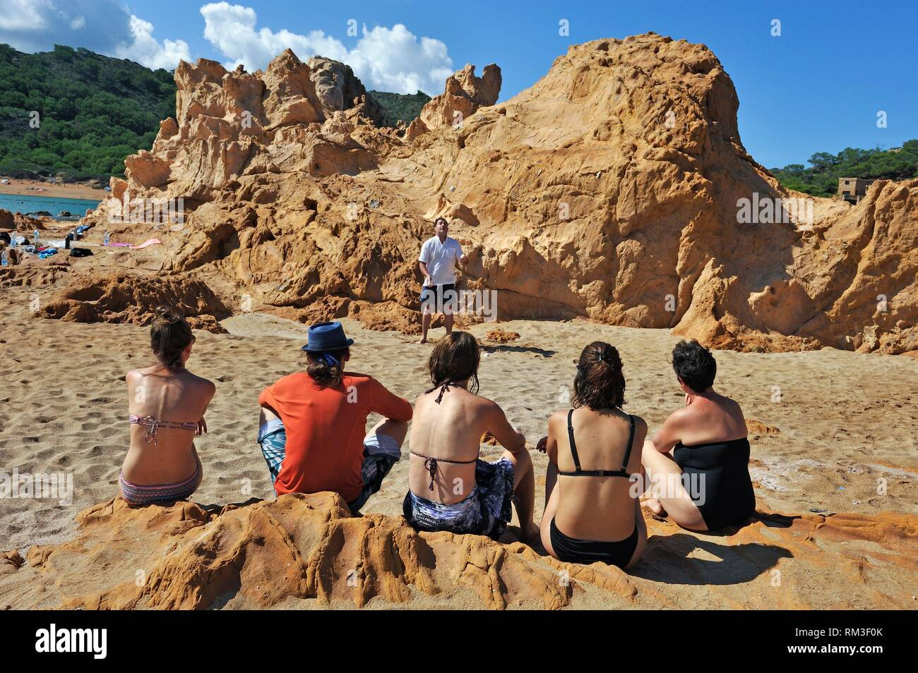 man juggling balls on the beach of an islet in the inlet Cala Pregonda near Cape Cavalleria on the North Coast of Menorca, Balearic Islands, Spain, - Stock Image