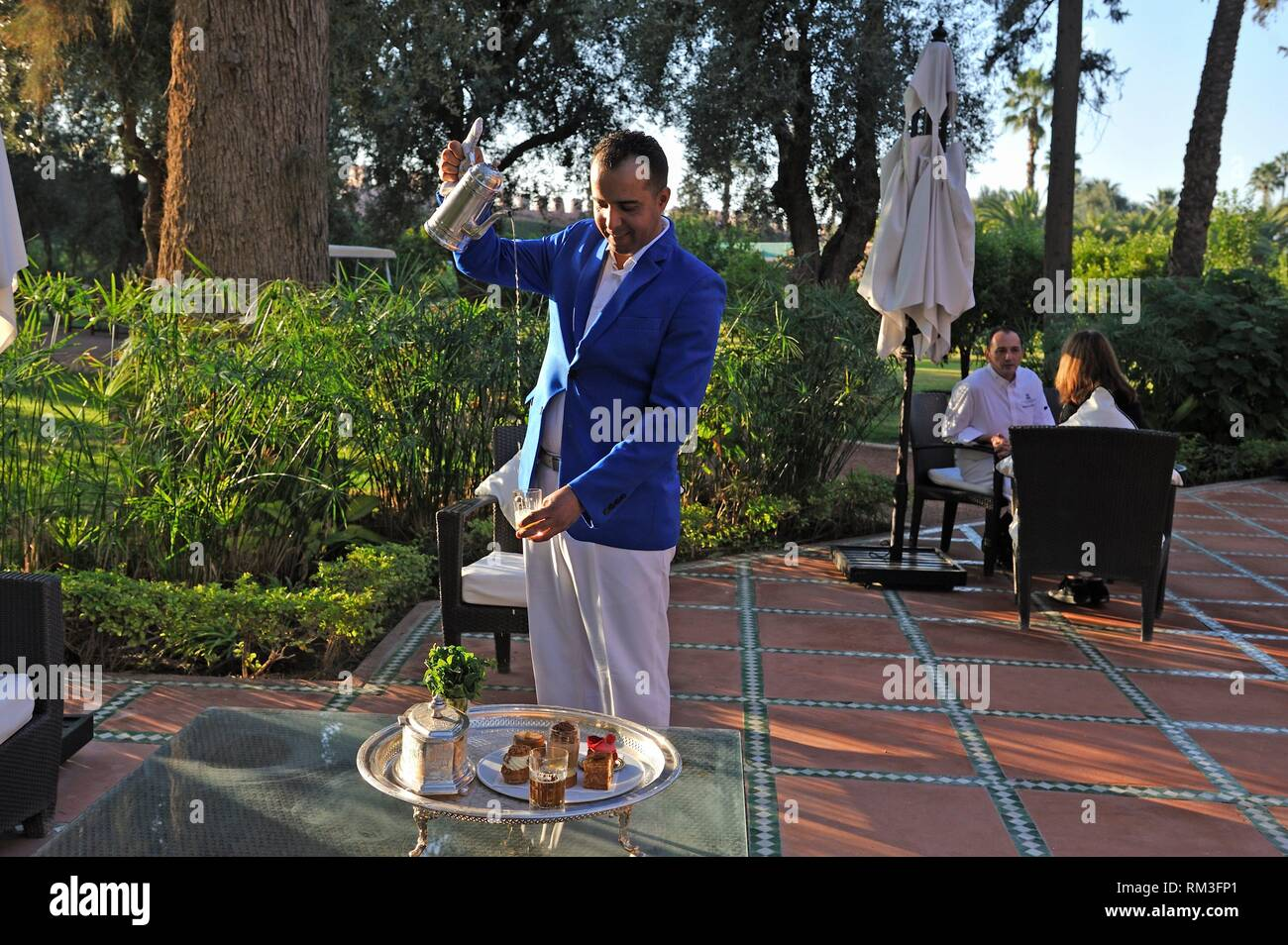 waiter serving mint tea, with pastries designed by Pierre Herme and made by Richard Bourlon, at the pavilion Menzeh within the gardens of the luxury - Stock Image