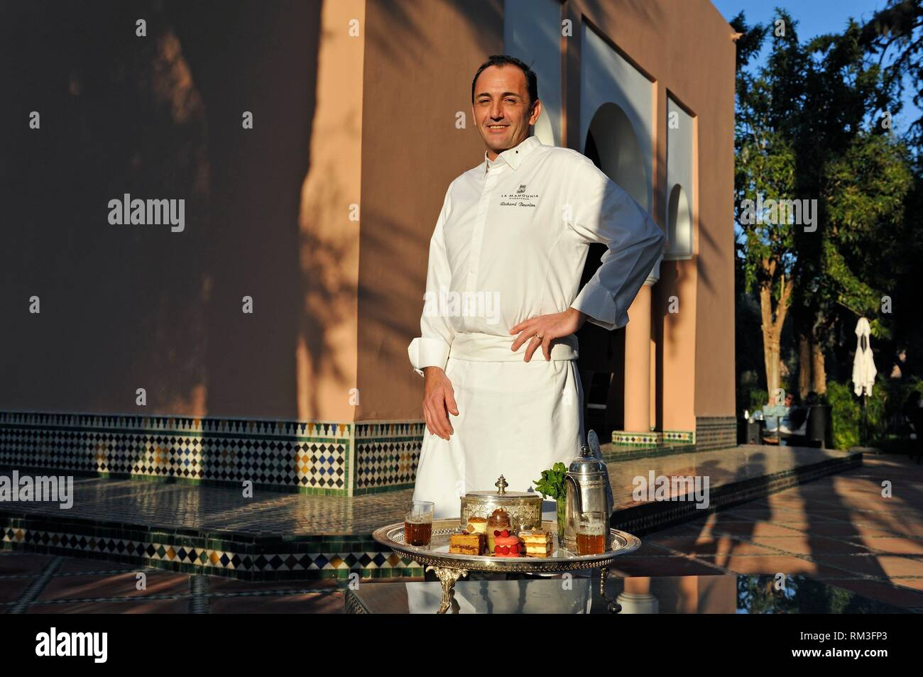 Richard Bourlon posing beside pastries designed by Pierre Herme and made by himself, served with mint tea at the pavillion Menzeh within the gardens - Stock Image
